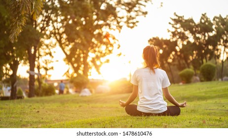 Pretty asian woman doing yoga exercises in the park. Used for relax and healthy concept