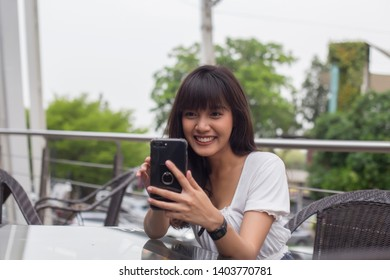 Pretty asian woman enjoy with cellphone in restaurant