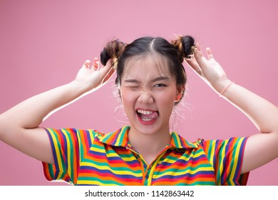 Pretty asian woman with funny face touching her hair on pink background
