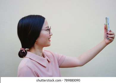 Pretty asian woman in glasses taking selfie with a smartphone