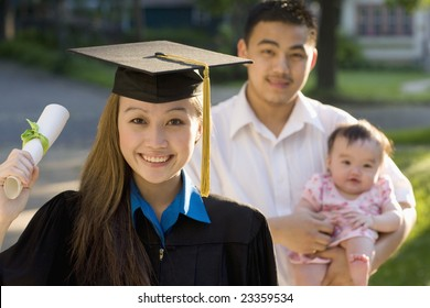 Pretty Asian woman graduating standing with husband and baby