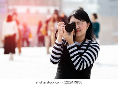 Pretty asian woman holding camera and shooting urban in Seoul, South Korea