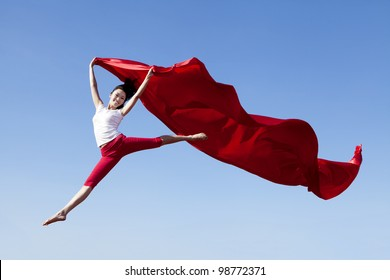 Pretty Asian Woman jumping with scarf shot against blue sky