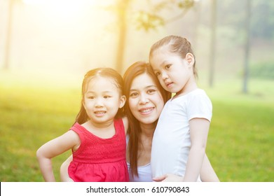 Pretty Asian woman looking at camera with smile while holding her preschool daughters in arms, little girl hugging her mother tenderly, morning with sun flare.