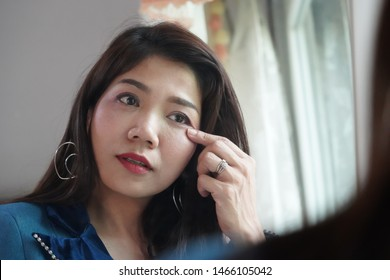 pretty asian woman looking mirror for checking her wrinkle