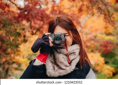 Pretty asian woman on wear winter cloth holding camera and shooting on beautiful autumn leave trees background in japan.