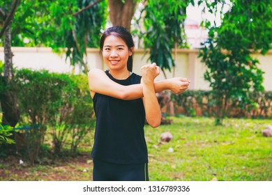 Pretty Asian woman pose warm up workout training exercise warm up with green garden background, selected focus.