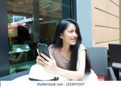 Pretty asian woman relaxing in the coffee shop and holding smart phone