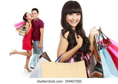 pretty asian woman with shopping bag, her friend at the background
