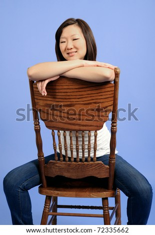 93f3f40fb53 Pretty Asian woman sitting backwards on an older wood chair in white  tanktop and blue jeans