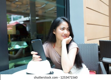 Pretty asian woman sitting with happily in coffee shop and holding smart phone