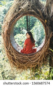 Pretty Asian woman is sitting on straw nest, Ubud, Bali.