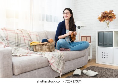 pretty asian woman sitting on sofa looking autumn outside of window and making seasonal knitting for winter coming and in the living room at home