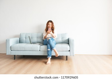 Pretty asian woman using smart phone at home