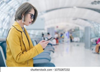 Pretty asian woman using smartphone on the airport terminal while waiting for flight,technology and travel concept