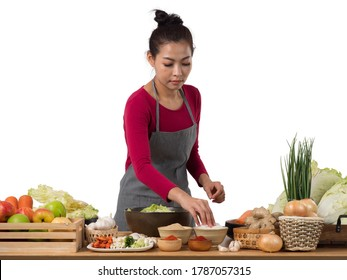 Pretty Asian woman wearing apron, preparing fresh vegetables, cutting all ingredients, putting all the spice to make Kimchi, famous Korean side dish.