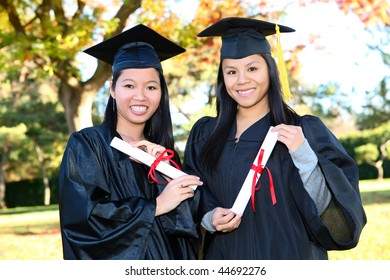 Pretty Asian woman wearing cap and gown holding diploma at graduation