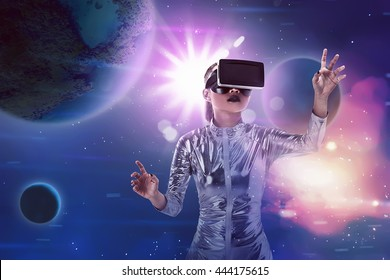 Pretty asian woman wearing silver latex jumpsuit and VR headset inside virtual world. Virtual reality concept