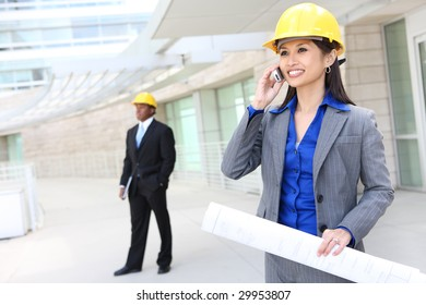 A pretty asian woman working as architect on a construction site