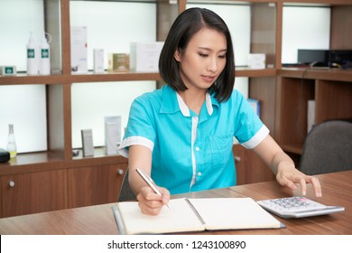 Pretty Asian woman working in spa salon and calculating while taking notes at working stand