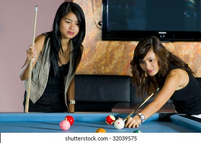 pretty asian women playing pool. focus on the one who is playing.