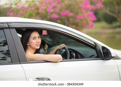 Pretty Asian women in a white car happy driving