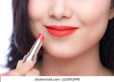 Pretty asian young woman applying red matt lipstick on her lips