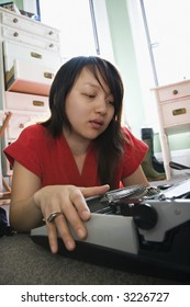Pretty Asian young woman lying on floor in red robe typing on typewriter.