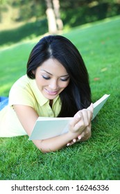 A pretty asian young woman reading book in park