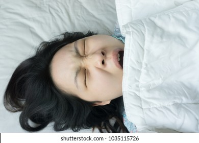 Pretty Asian young woman yawning in the morning time. she is too lazy to waking up from soft bed on holiday and want to sleep again.