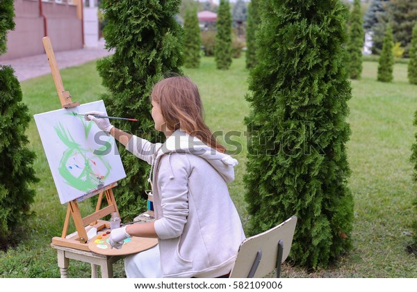 Pretty attractive artist begins to painting which depicts  colorful butterfly, sitting with back to photographer and behind wooden easel, holds palette smeared in paint in large park green day outdoor