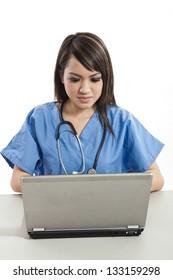 Pretty attractive asian filipino nurse working on laptop