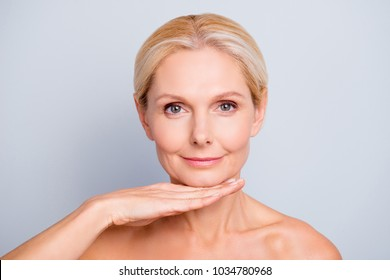 Pretty, attractive, charming,  woman demonstrate, show, present her perfect skin after peeling, lotion, mask, isolated on grey background, holding hand under chin, treatment, therapy concept