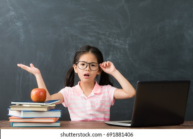 pretty attractive little girl children using computer studying having problem in chalkboard background and face to camera showing confused emotion.