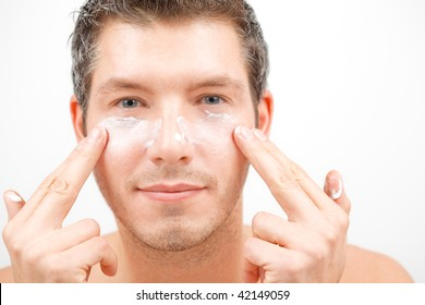 Pretty attractive man beautify applying rejuvenate cream on face for better male macho appearence