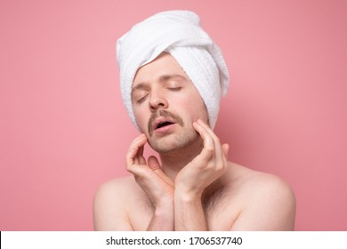 Pretty attractive man beautify making face massage for better male macho appearence. Studio shot on pink wall.
