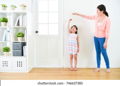 pretty attractive mother with cute little daughter measuring growth record when they standing in wooden floor with white background together.