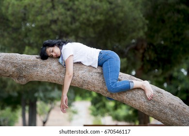 Pretty attractive woman wearing causal clothes over worked and stressed feeling relaxed sleeping in a tree in a green park.