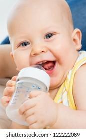 Pretty baby boy drinking water from bottle