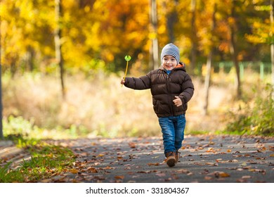 Pretty baby boy running in autumnal park - beauty autumn season