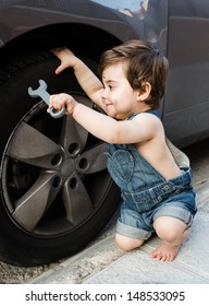 Pretty baby dressed as mechanic smiling and repairing a real car