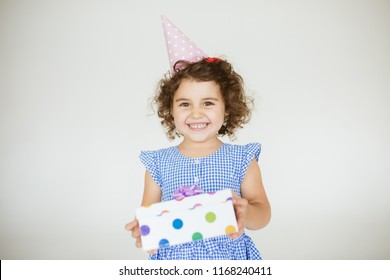 Pretty baby girl with dark curly hair in blue dress and birthday cap happily looking in camera with gift box in hands over white background