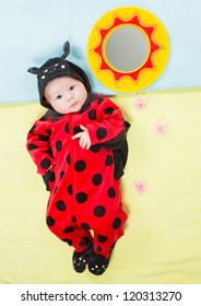 Pretty baby girl, dressed in ladybug costume on green background  The concept of childhood and holiday