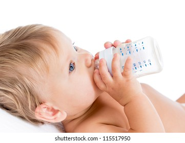 Pretty baby girl drinking milk from bottle