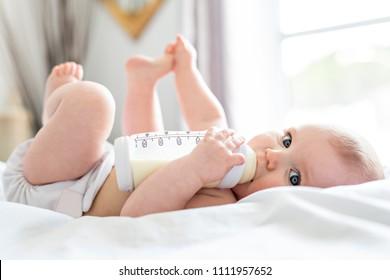 Pretty baby girl drinks water from bottle lying on bed. Child weared diaper in nursery room.