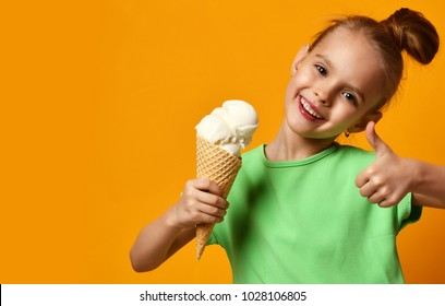 Pretty baby girl kid eating licking vanilla ice cream in waffles cone on yellow background