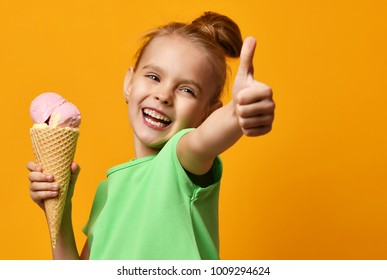 Pretty baby girl kid hold banana and strawberry ice cream in waffles cone on yellow background and show thumbs up sign with free text copy space