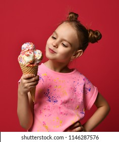 Pretty baby girl kid hold big ice cream in waffles cone with raspberry happy smiling ready to eat on red background