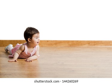 Pretty baby girl lie on the wood floor looking away on a isolated background