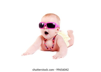 Pretty baby girl in pink sunglasses and colored necklace lying on white background
